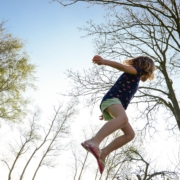 healthy energetic child jumping in woods on spring day