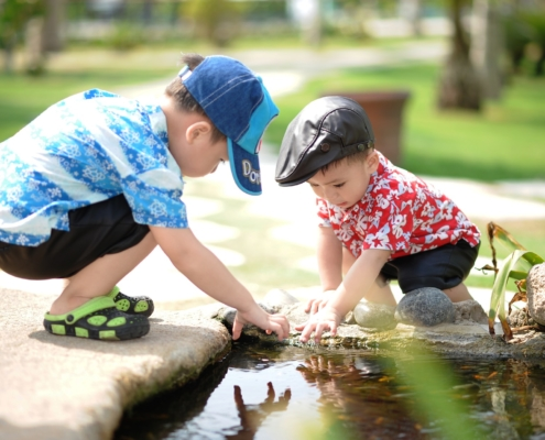 boys playing by a stream