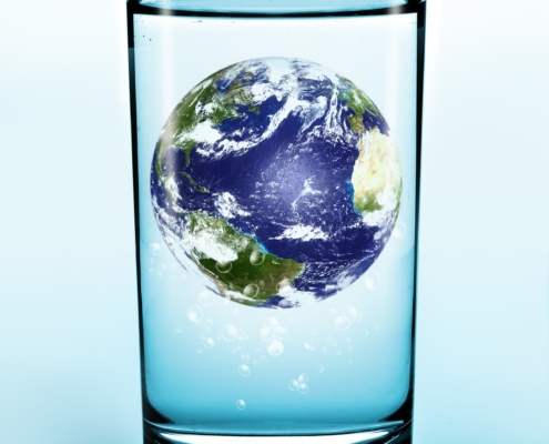 glass of pure water with earth floating in center to symbolize trace minerals from the earth