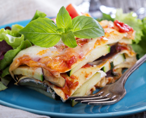 Vegetable lasagna with zucchini, tomato and eggplant, gluten free; on a plate with garnish