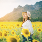 Happy woman in sunflower field smiling