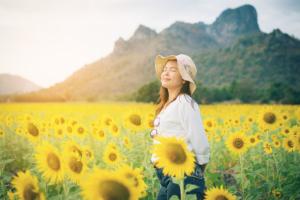 Happy woman in sunflower field smiling