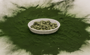 bowl of chlorella tablets surrounded by green chlorella powder on a table