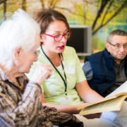 Nurse reading book to elderly group of people