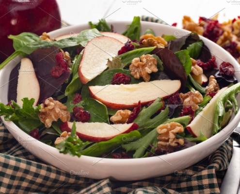 winter greens walnut cranberry apple salad in white bowl