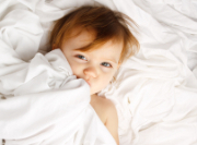 child with fever under a blanket
